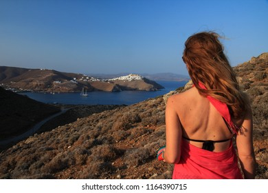 A woman with her back turned to camera enjoying the view of the Greek island of Astypalaia