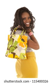 a woman with her bag over her shoulder looking over her shoulder with a smile on her lips.