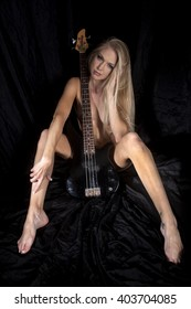 woman with her bass guitar on black