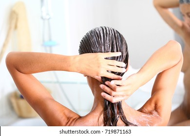 woman in her bathroom applying a care on her hair