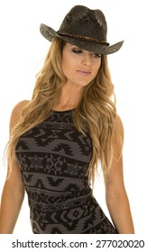 A woman in her black and gray dress, wearing her western hat.