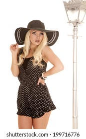 a woman in her black and white polka dot outfit and a floppy hat.