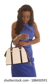 A woman in her blue dress looking down into her purse.