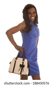 A woman in her blue dress smiling holding on to her purse.