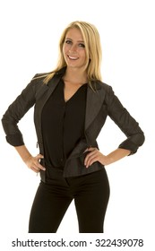 A woman in her business attire with her hands on her hips with a smile.