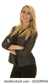 a woman in her business jacket with a smile and her arms folded.