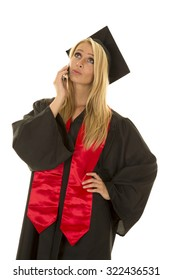 a woman in her cap and gown on her cell phone.