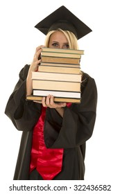 a woman in her cap and gown peeking over a stack of books.