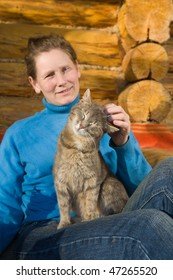 Woman with her cat sitting near her country house