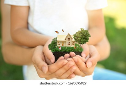 Woman and her child holding their dream house with beautiful green lawn on sunny day, closeup