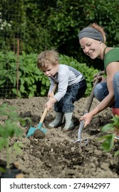 Woman and her child planting cultivating together in garden yard