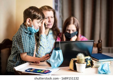 A woman and her children study through a laptop online because schools are closed due to quarantine. Focus on medical mask hanging on computer. Mom calls the teacher, asks for help
