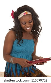 a woman in her colorful dress working on her tablet with a smile on her face.
