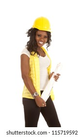 a woman in her construction clothes with hard hat and her blue prints with a smile on her face.
