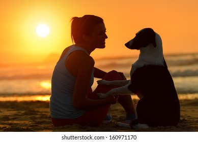 Woman with her cute dog in the beach on golden sunset background. Girl enjoying her pet friendship and affection towards beautiful sun and sea.