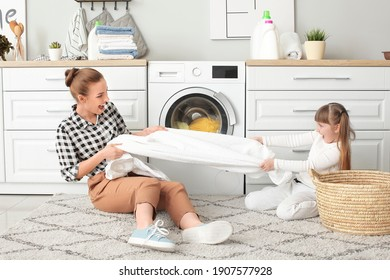 Woman and her cute little daughter having fun while doing laundry at home