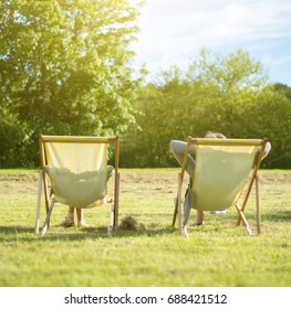 Woman and her daughter enjoying the sun in chaise lounge. From the back.