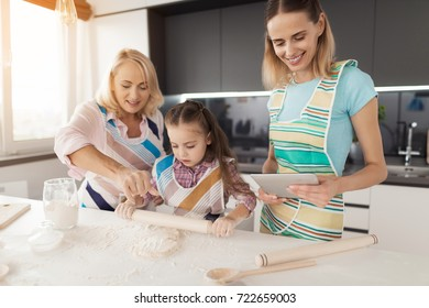A woman, her daughter and grandmother prepare a homemade biscuit. A woman holds a gray tablet in her hand and checks it with a prescription. Grandma and and the girl are kneading the dough