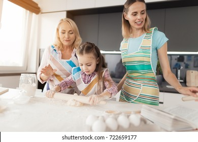 A woman, her daughter and grandmother prepare a homemade biscuit. The girl rolls the dough with a rolling pin. Her grandmother and mom help her. They are dressed in kitchen aprons