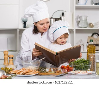 Woman with her daughter are looking recipe in culinary book together at home.