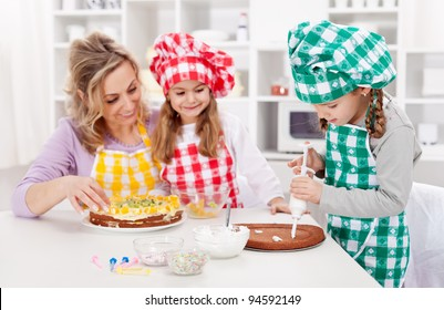 Woman and her daughters in the kitchen making a cake together