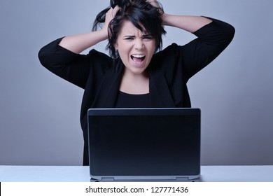 woman at her desk working on a laptop computer pulling out her hair