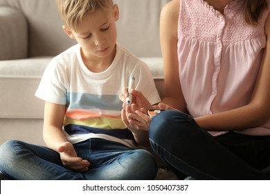 Woman and her diabetic son with lancet pen and glucometer taking blood sample at home