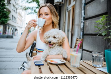 Woman with her dog enjoy in street cafe