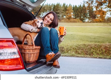 Woman with her dog have a tea time during their autumn auto travel