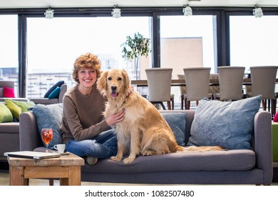 Woman and her dog sitting on sofa. Looking at camera