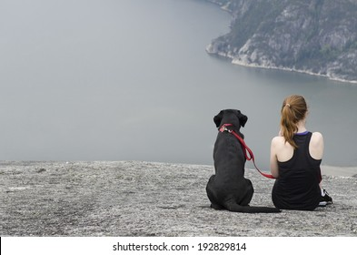 Woman with her dog sitting on a cliff
