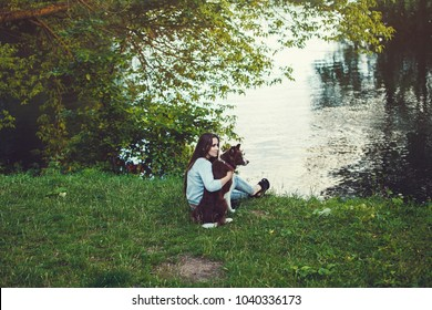 Woman and her dog sitting outdoor. Girl loving and hugging tightly her dog and watching on river
