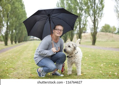 Woman and her dog under an umbrella. She is looking into the camera with a friendly smile. Clothing is casual.