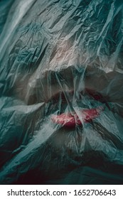 Woman with her face covered by a plastic sheet or bag with open mouth and red lips struggling to breath or screaming in an evocative conceptual image of suffocation and crime