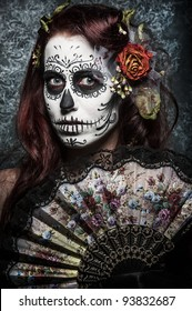 a woman with her face painted as a traditional day of the dead sugarskull mask