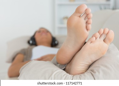 Woman with her feet up listening to music on the sofa