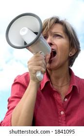 Woman in her fifties shouting through a megaphone.