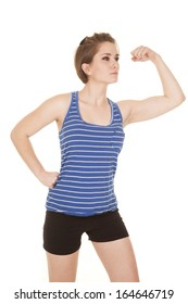 A woman in her fitness clothes flexing her arms.