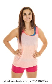 A woman in her fitness clothing with her hands on her hips.
