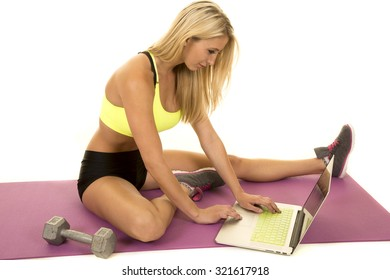 a woman in her fitness clothing looking for a workout on her laptop.
