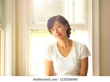 A woman in her forties sits on a window sill.
