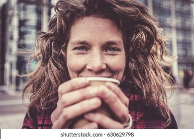 Woman In Her Forties Warming Her Hands On Coffee Cup