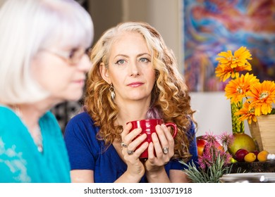 A woman and her friend sit in kitchen