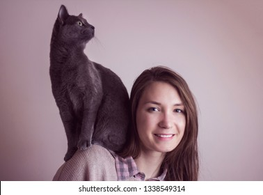 Woman with her funny pet cat sitting on her shoulders