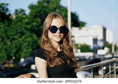 Woman with her hair in glasses with smiles, city portrait