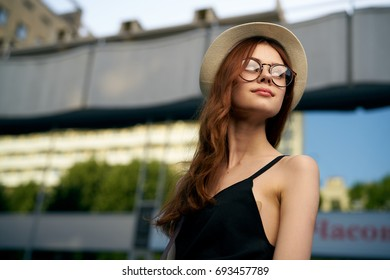 A woman with her hair in her hat and glasses looking away