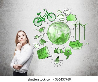 A woman with her hand to the chin thinking, symbols of alternative energy sources painted in green colours on a white poster behind her. Green Earth in the middle. Concept of clean environment.