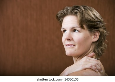 Woman with her hand on her shoulder looking left