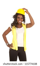a woman with her hand on top of her hard hat with a big smile on her face.