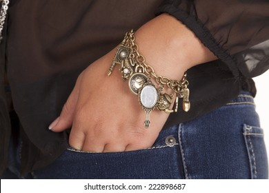 a woman with her hand in her pocket with bracelet charms on her wrist.